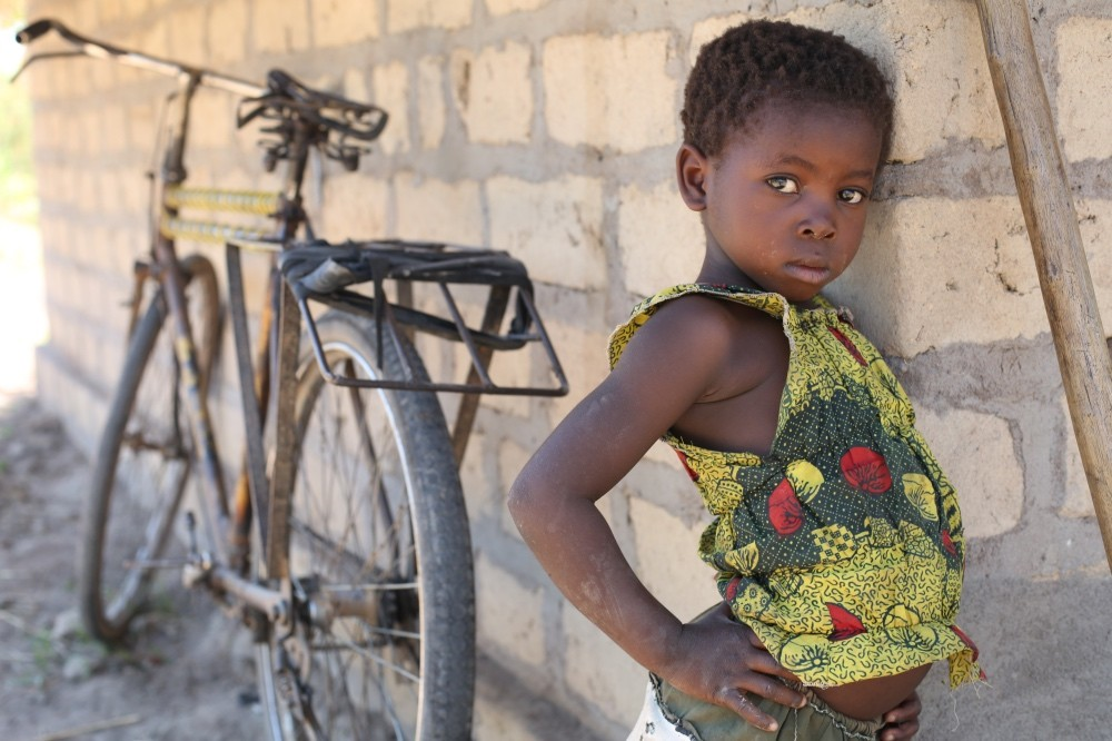 Young girl peeping around corner of wall in rural village in Zambia