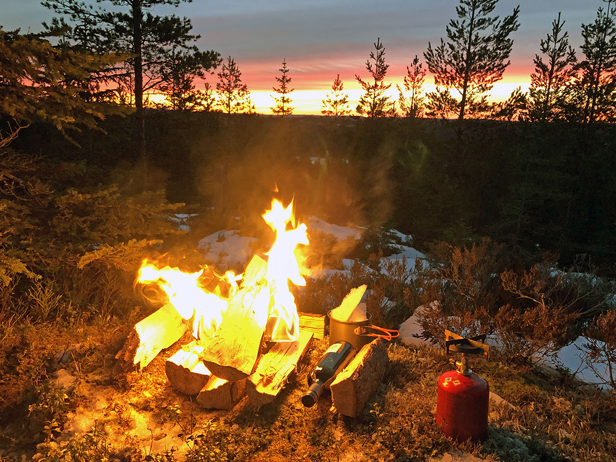 Een vuurtje tijdens het winterkamperen in Zweden
